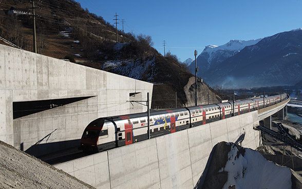 A double-decker train approaches a tunnel along a viaduct in the mountains.