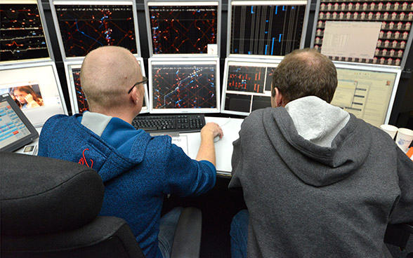 Two men sit at 10 monitors on which mainly red and blue lines can be seen.